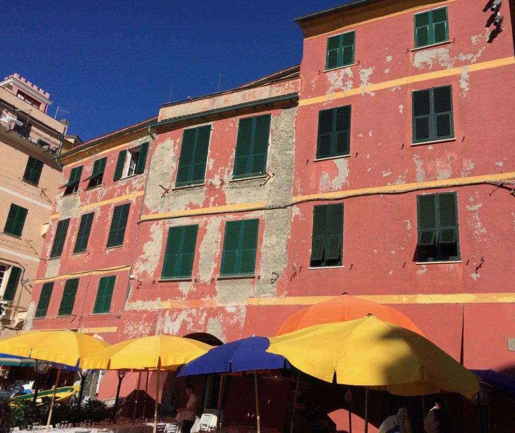 pink building in Vernazza, Cinque Terre with colorful beach umbrellas