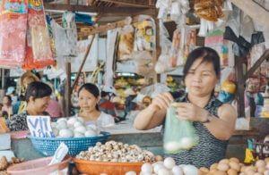 Photo of street vendor weighing garlic at a Vietnamese street market