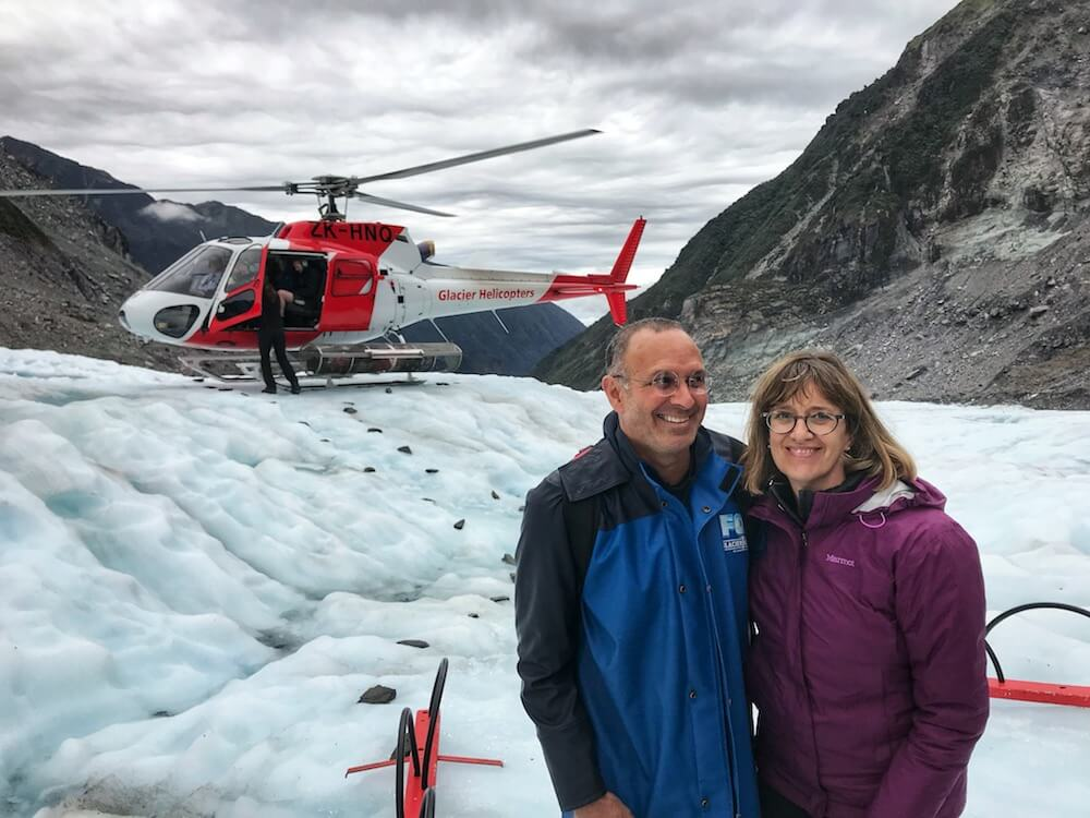 The two of us standing on Fox Glacier with the helicopter in the background