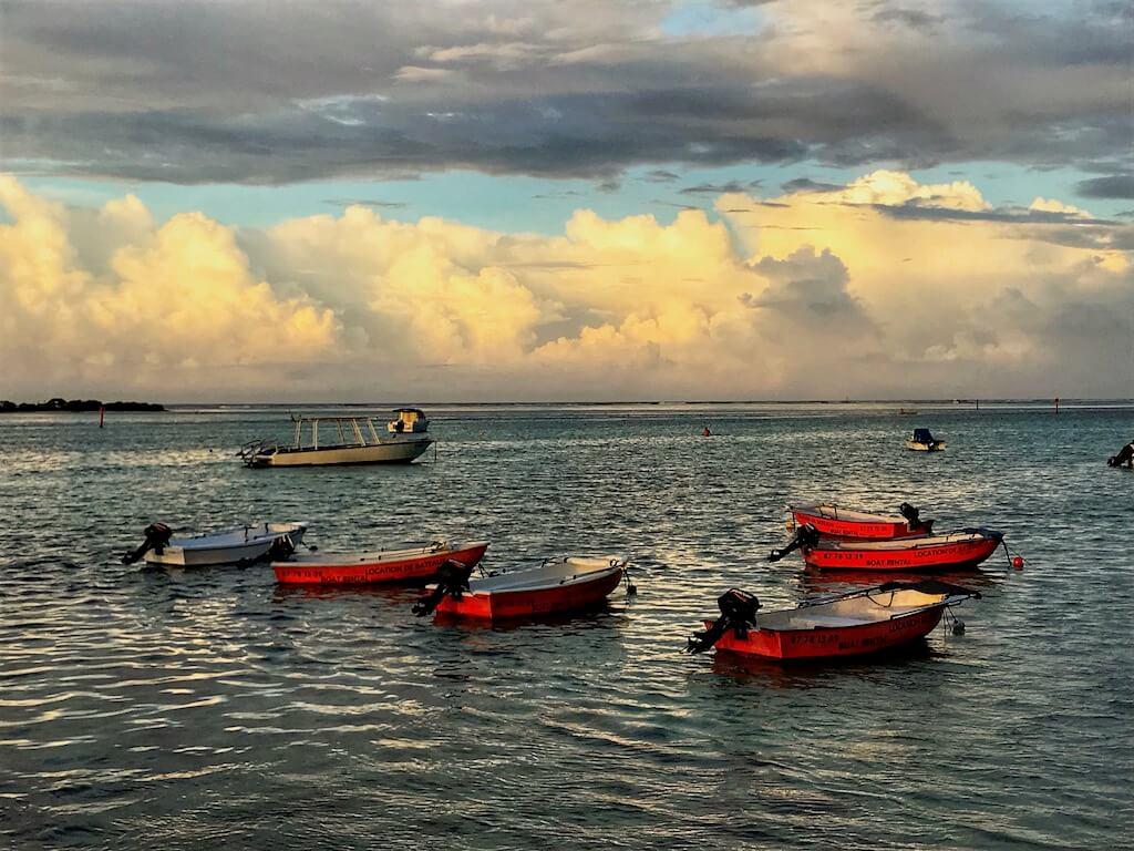 boats at sunset at Les Tipaniers Beach Moorea