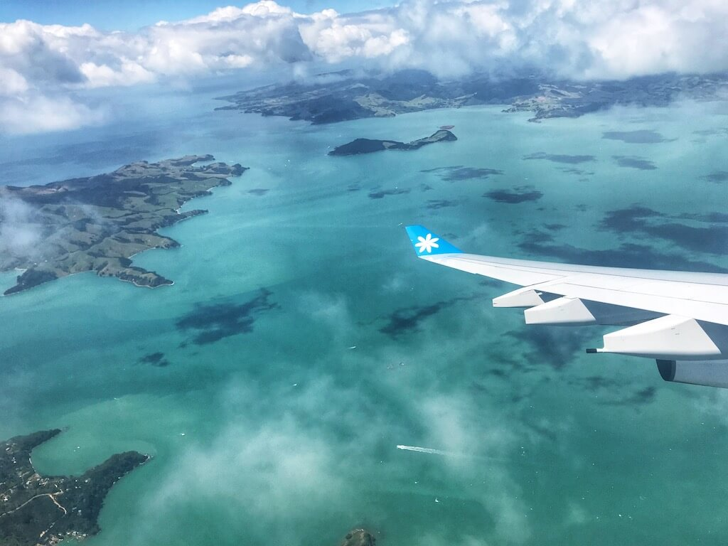 plane wing over a turquoise ocean and New Zealand islands