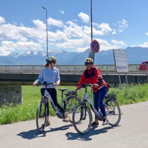 two women on bicycles by a bridge