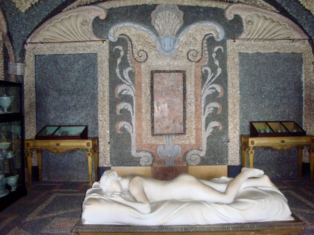 supine marble statue inside underground stone grotto