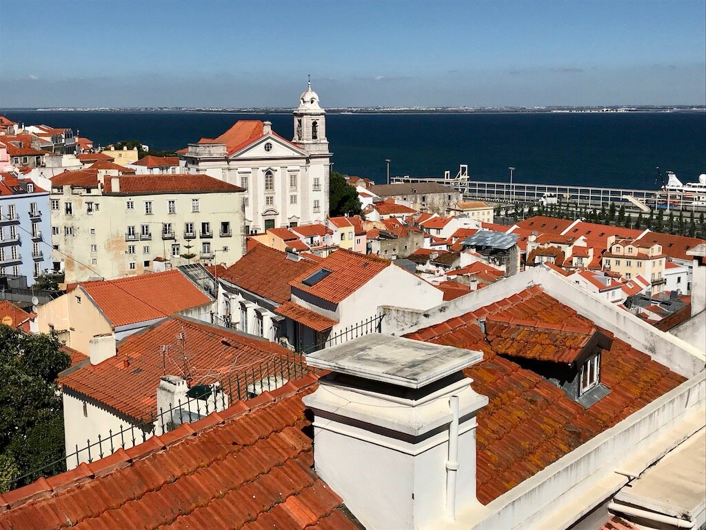 Viewpoint in Lisbon looking down on orange terracotta roofs all the way to the sea