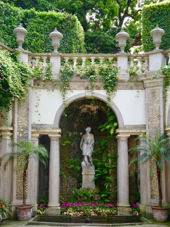 marble statue underneath a facade in the garden