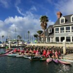 a dozen women in Santa Hats on SUP boards in a bay