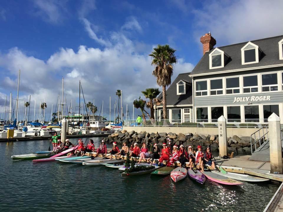 a dozen women in Santa Hats on SUP boards in a bay