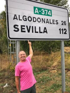 Man pointing at Algodonales street sign