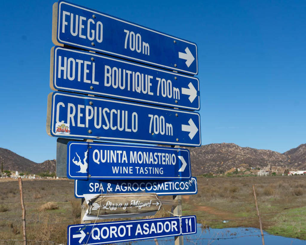 blue road sign with arrows pointing to best wineries in valle de guadalupe