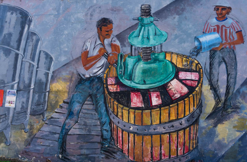 colorful mural of a man crushing grapes in a barrel