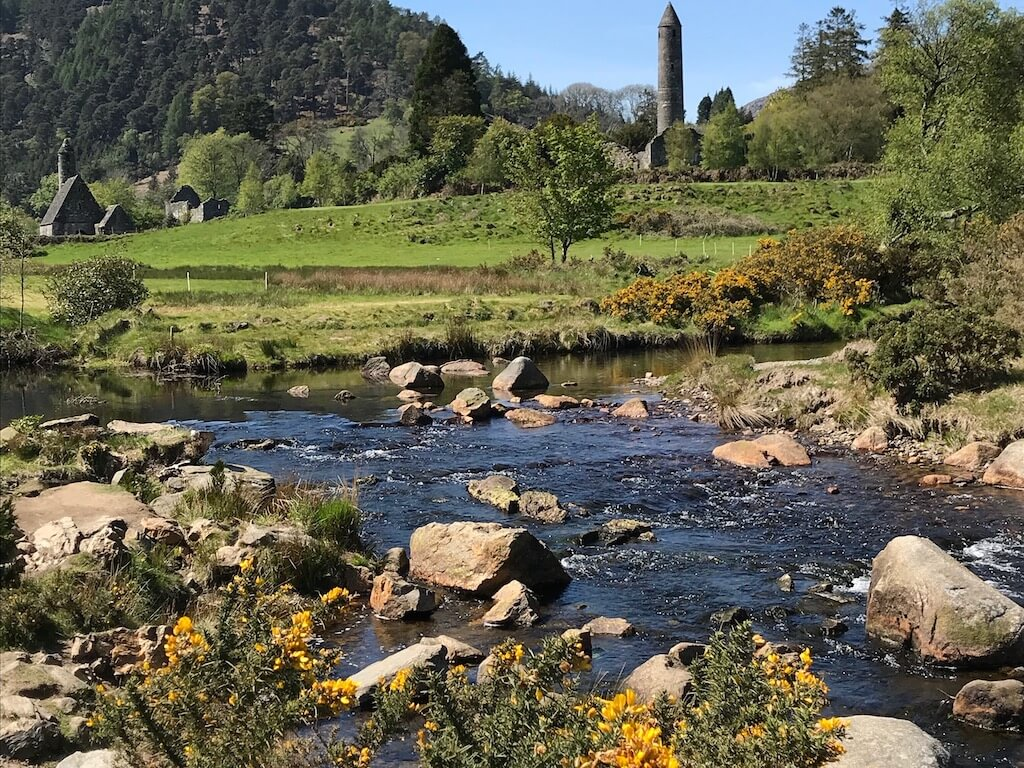 river with yellow flowers and abbey spire in background
