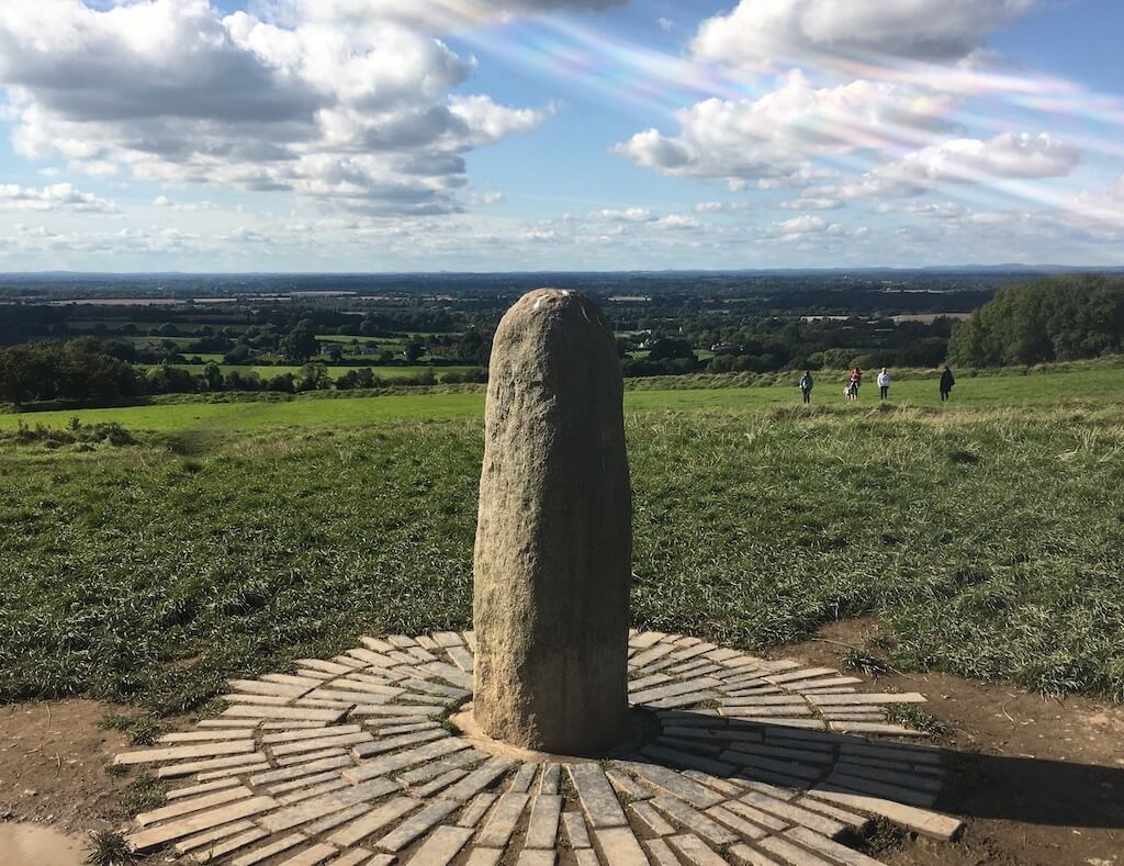 photo of a stone phallus like shape on a hill