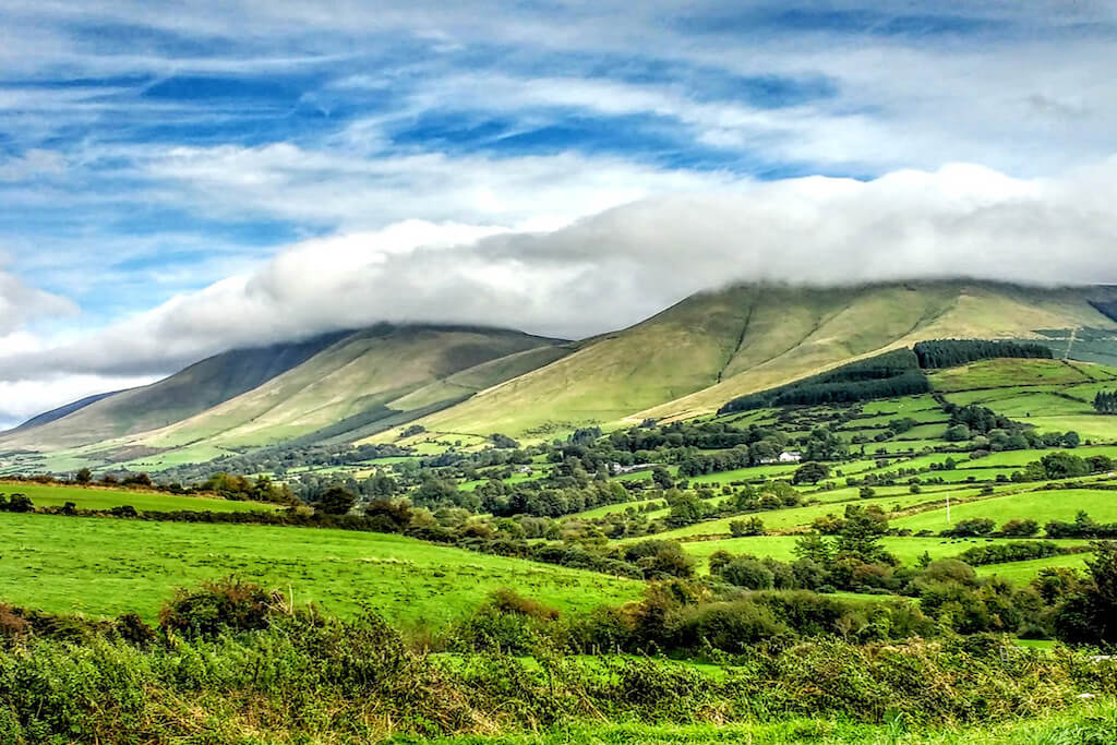 Green meadow with green hills and a sultry summer sky with wispy clouds at Glen of Aherlow tipperary