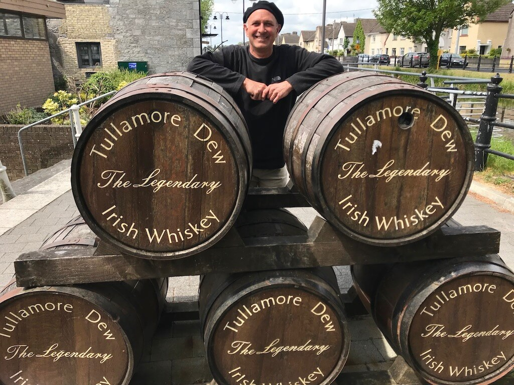 Man next to whisky barrels at Tullamore Dew