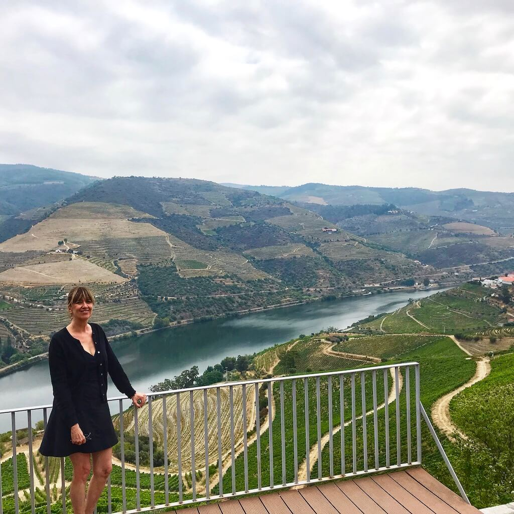 woman standing with sweeping vista and river behind her in Douro Valley