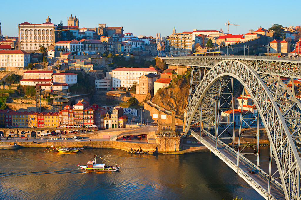 Skyline Porto with famous Dom Luis bridge and traditional rabelo boats on Duoro river. Portugal