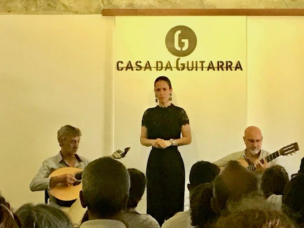Female fado singer accompanied by two guitarists at Casa da Guitara