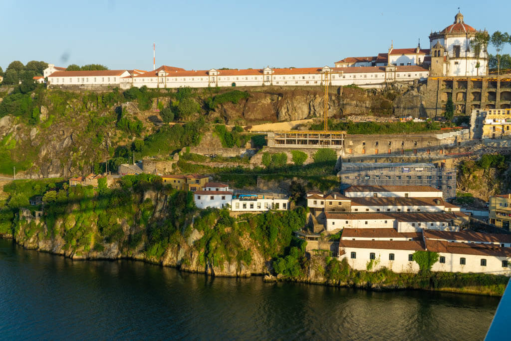 sunset view of warm light on the Douro River with white buildings in the background