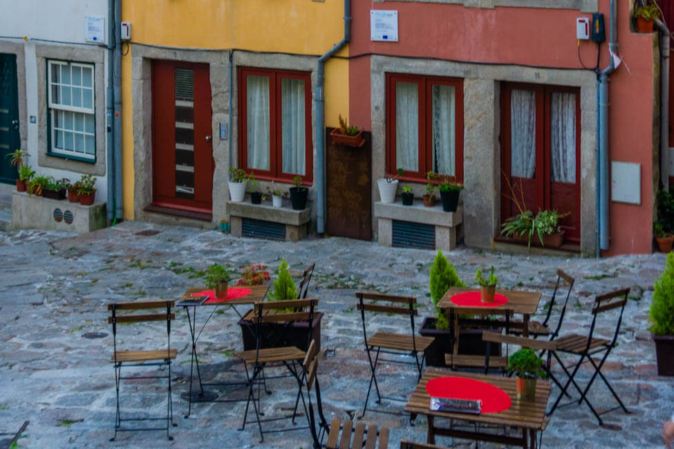 red chairs on a cobblestoned street in front of colorful building facades in Porto