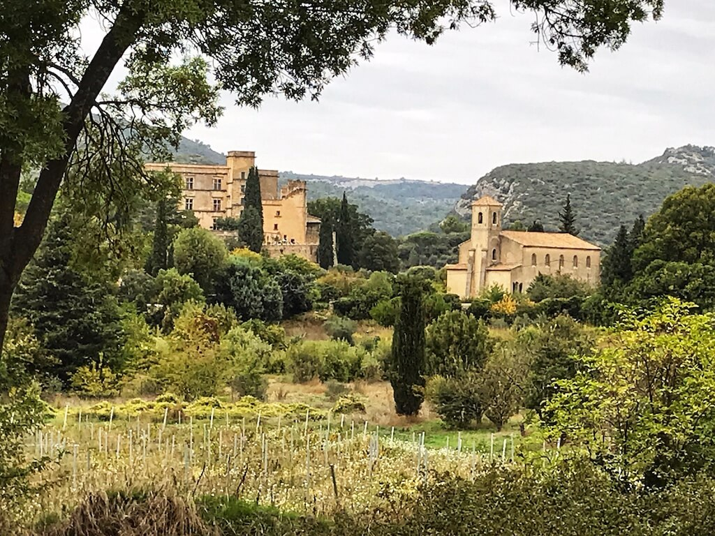 a stone castle seen through a field in Lourmarin