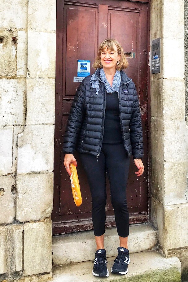 The same woman 32 years later holding a baguette in front of the same door