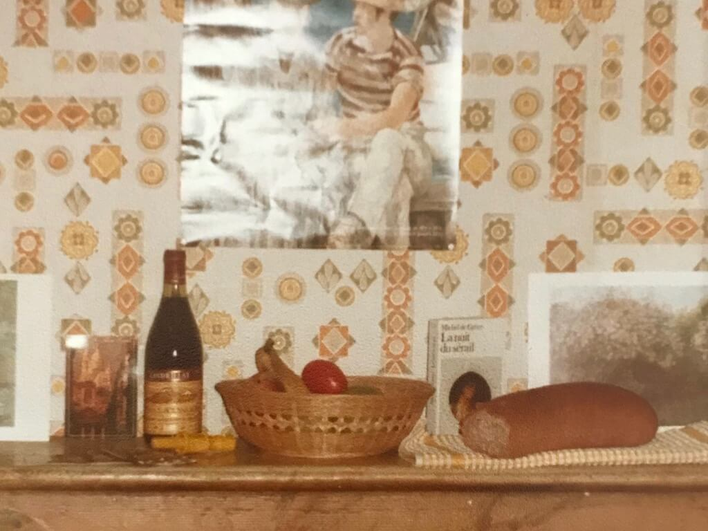 photo of fireplace mantle with a bottle of wine and bread