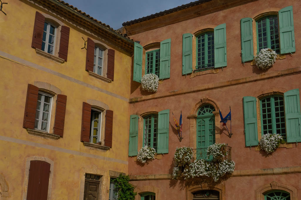 terracotta orange and yellow stone buildings with colorful shutters and white flowers draping from windows