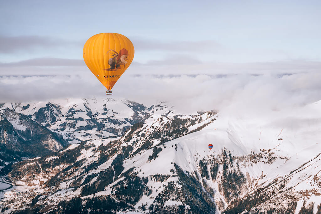 Brightly colored balloons floating above snowy mountain peaks in Chateau d'Oeux