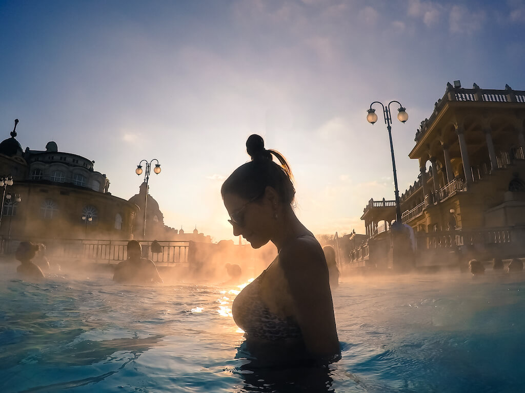 Steam rising around a woman in a thermal bath in Budapest during winter in Europe