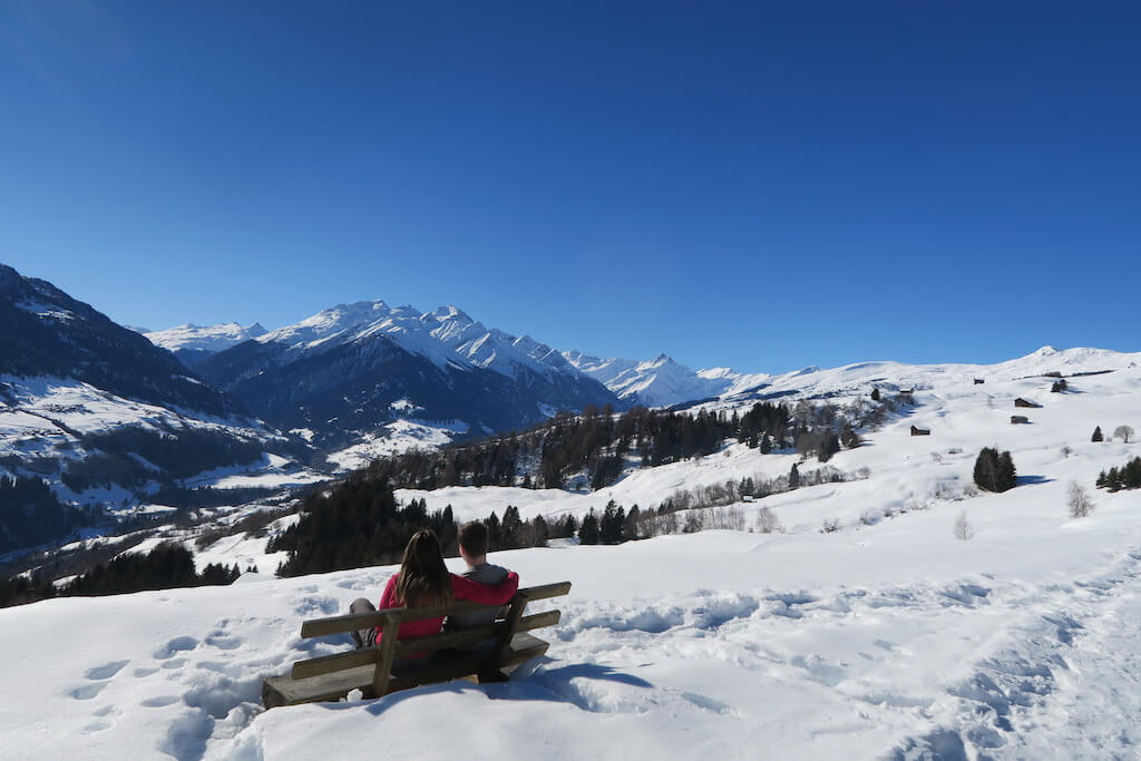 couple sitting on a bench high on a snowy mountain to experience winter in Europe