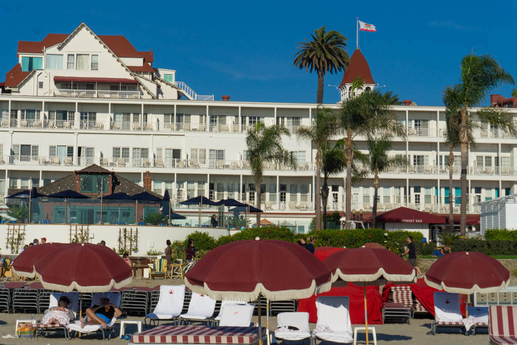 red beach umbrellas in front of Hotel Del in Coronado