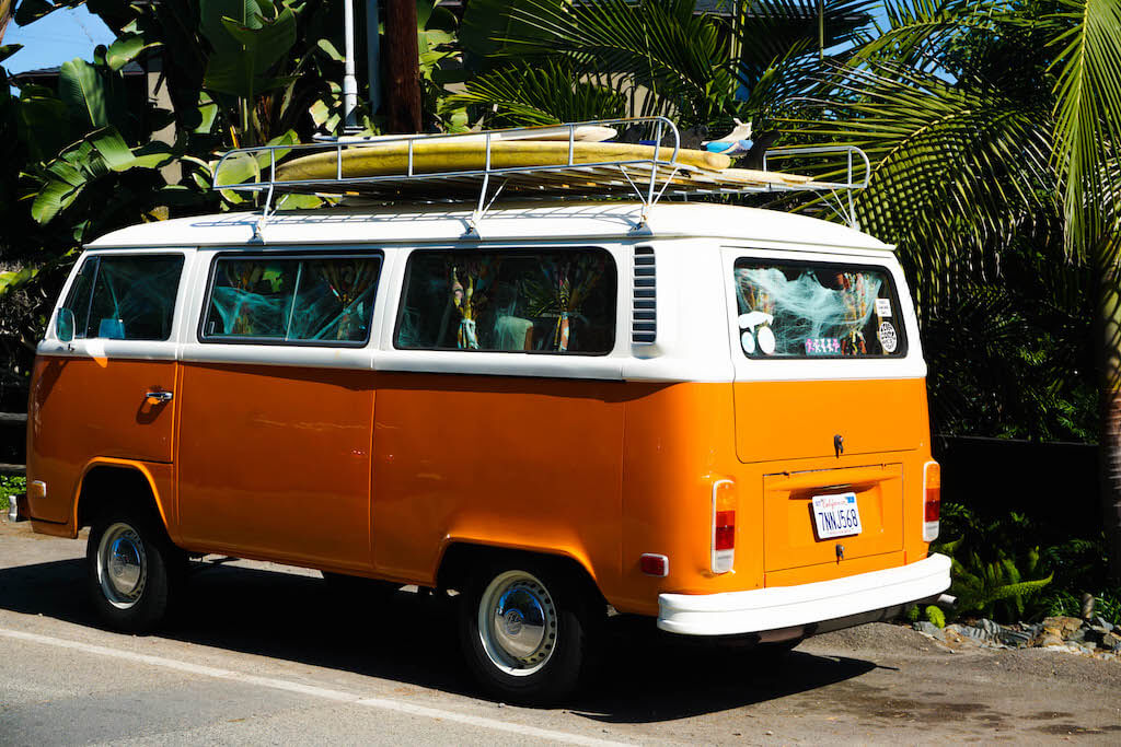 orange VW van with a surfboard on top