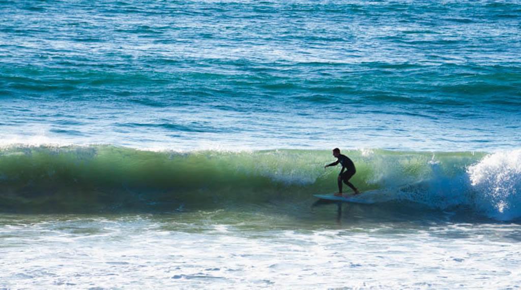 a surfer riding inside a tubular wave