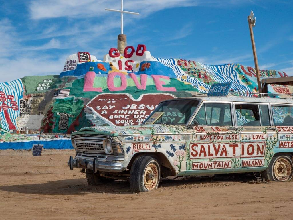 Old car with creative graffiti and colorful sculpture