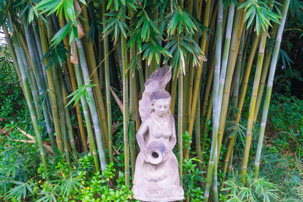 statue of a woman in a bamboo forest