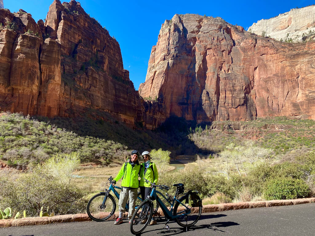 two cyclists on trail with cliffs in Zion Canyon