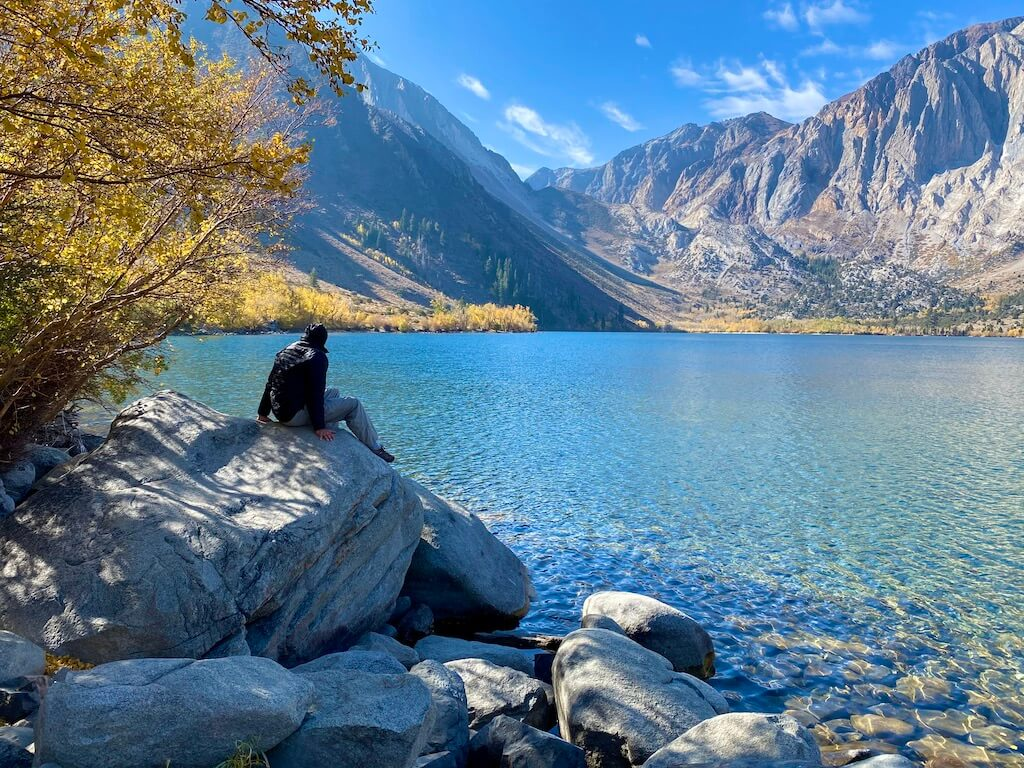 Man on a rock lakeside with Sierra mountains in the distance