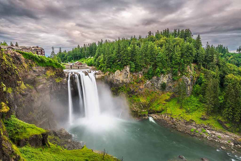 waterfall surrounded by forest and moody clouds