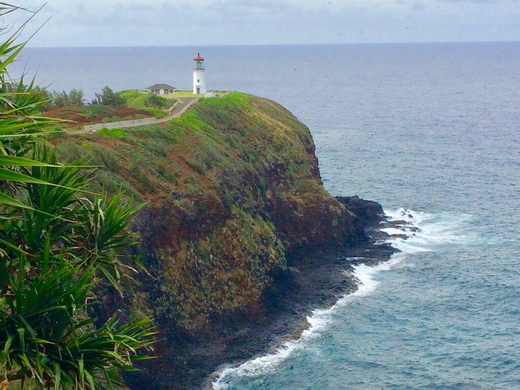 Lighthouse on steep peninsula above ocean