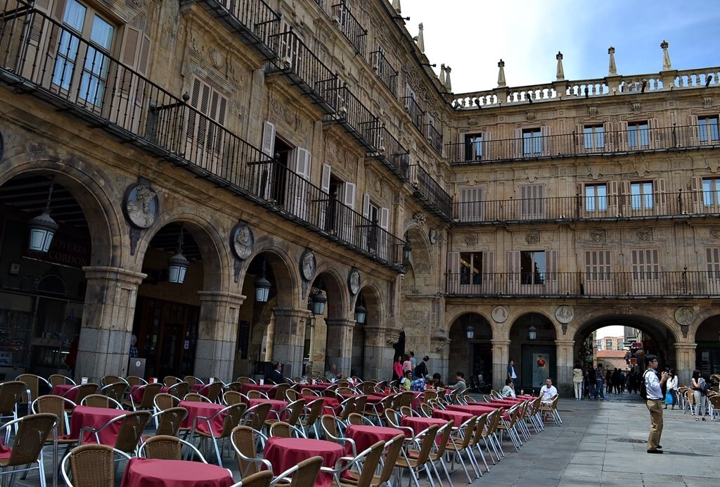 historic Spanish square with round tables out front