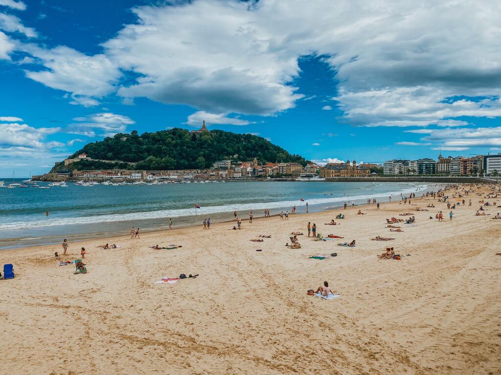 wide sandy beach in San Sebastian with cityscape around it