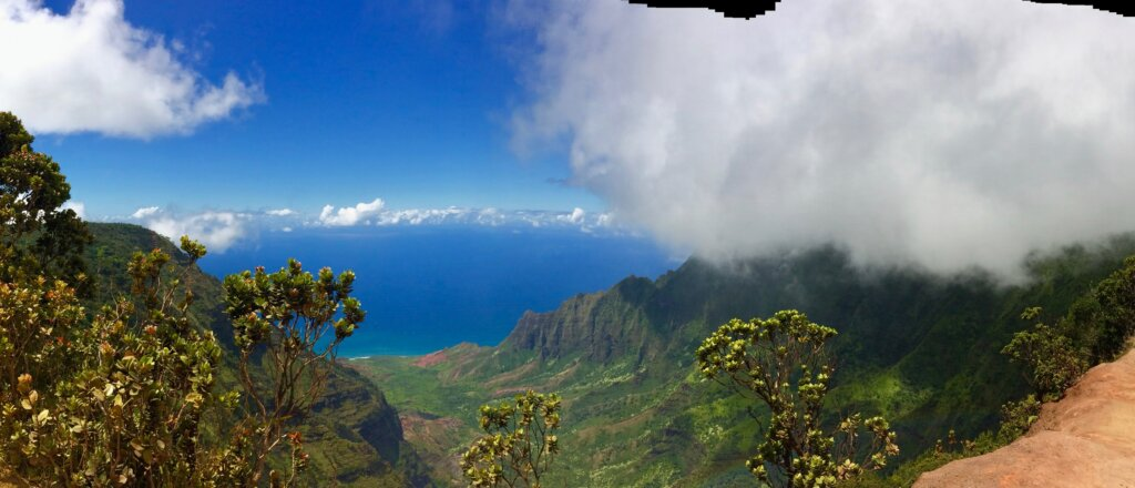 Green Napali cliffs under puffy white clouds giving way to the bright blue Pacific Ocean