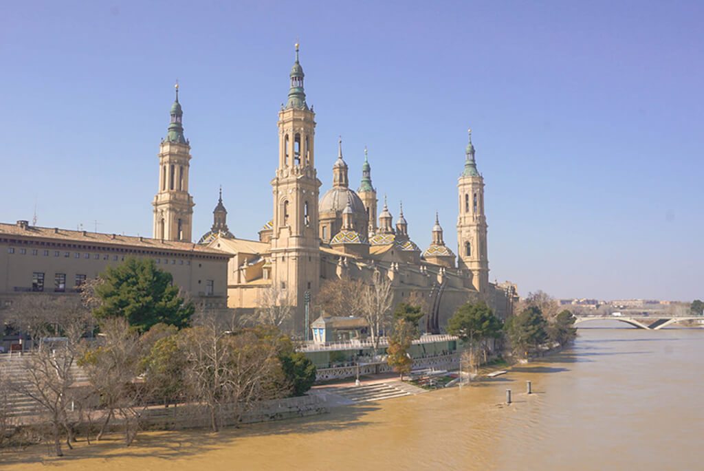 Historic Spanish building with tile roof on a river