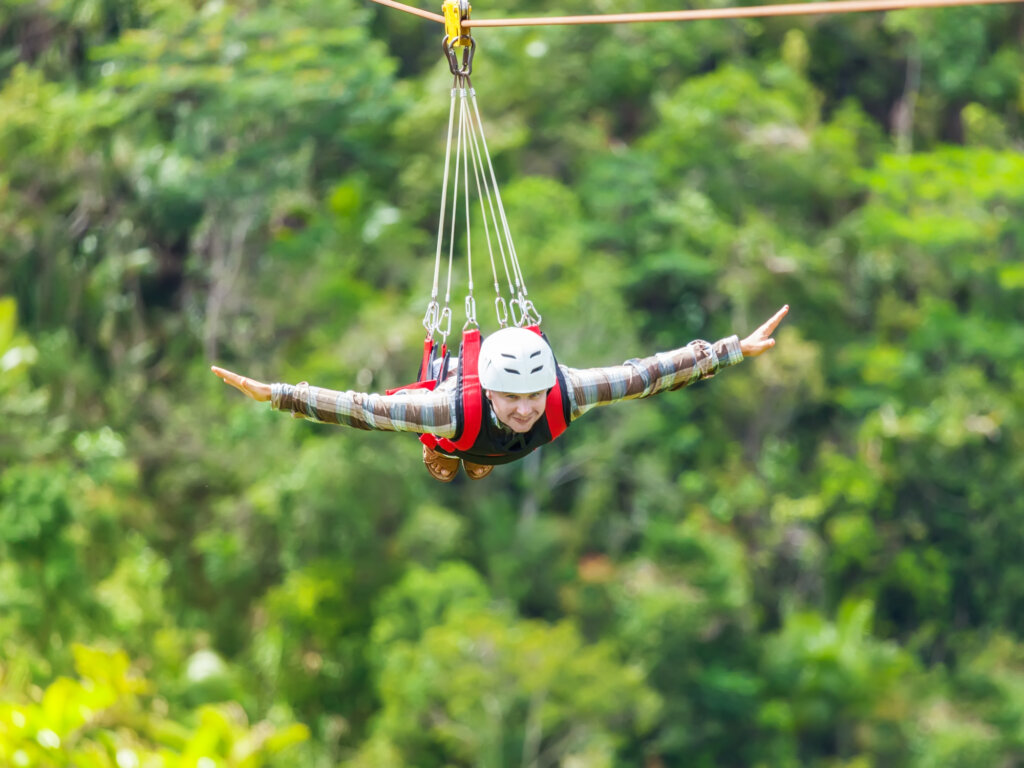 person with arms out ziplining
