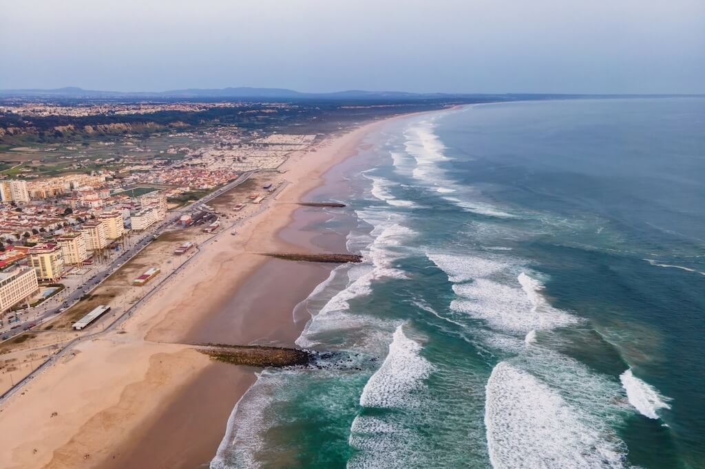 Aerial view of Costa da Caparica landscape at sunset, view of the majestic beach with rough Atlantic Ocean rolling on the shoreline, Setubal, Portugal.