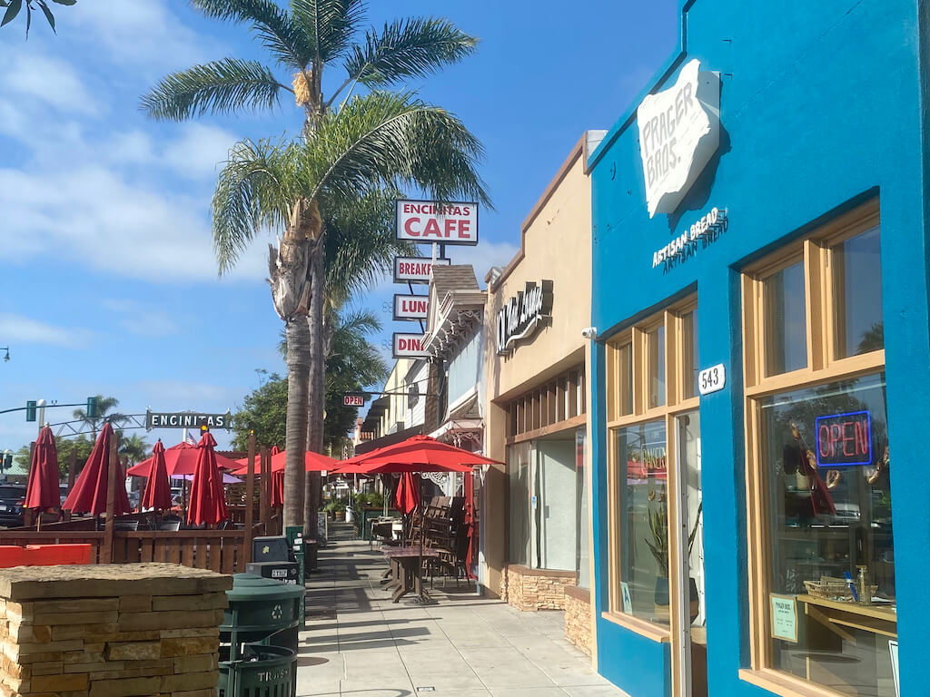 Street view of shops with Encinitas sign in background