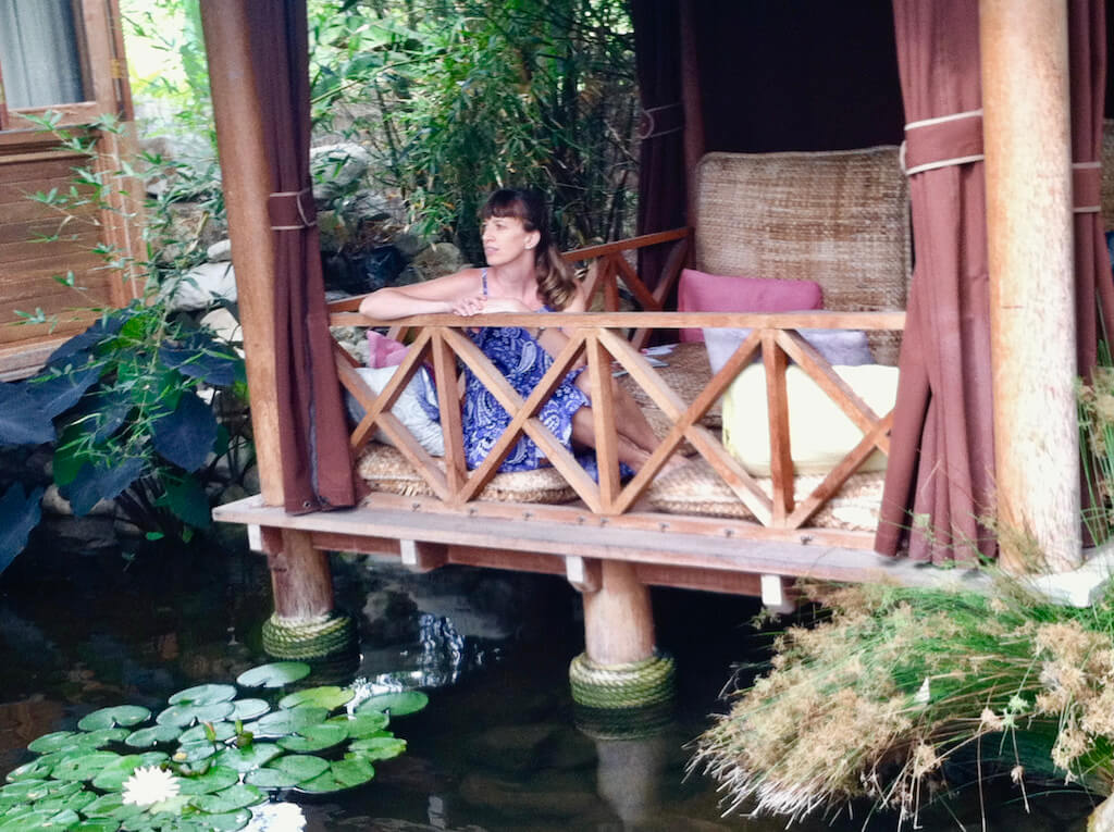 woman in a palapa looking out over lily pads in a pond