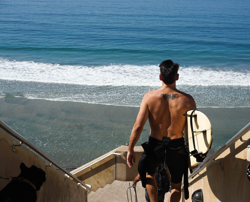 surfer walking down the steps