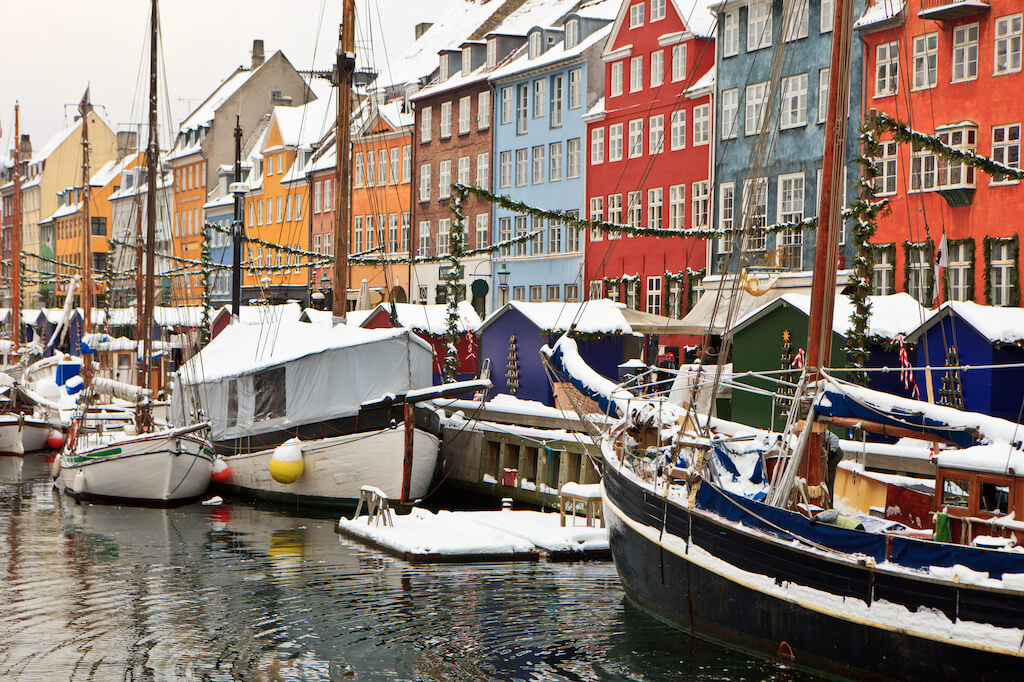 colorful buildings and boats in Copenhagen with a dusting of snow